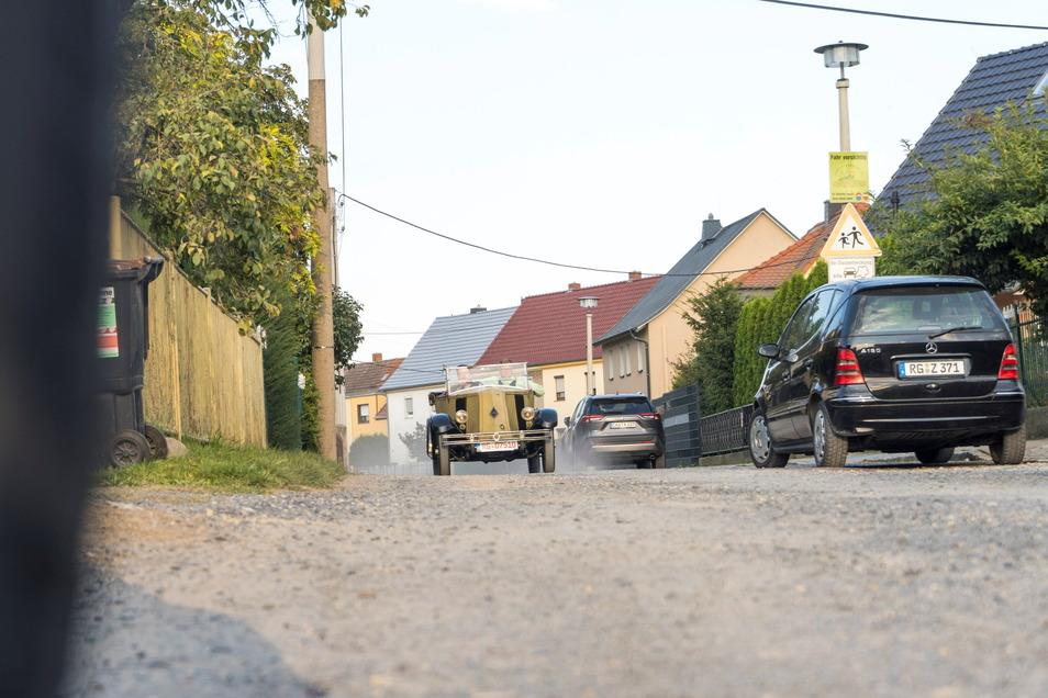 Ein Oldtimer fährt auf dem nicht asphaltierten Abschnitt der Dr.-Rudolf-Friedrichs-Straße in Riesa. Aber egal ob altes Auto oder neues: Schon bei geringem Tempo entsteht Staub, wenn es lange trocken war. Das soll sich bald ändern.