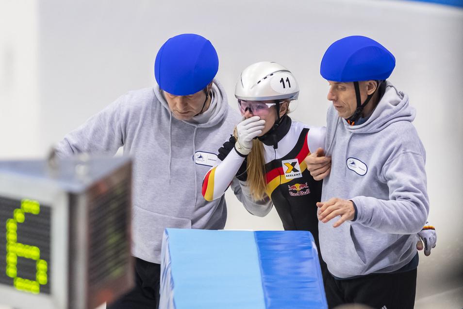 Anna Seidel muss sich von Helfern vom Eis bringen lassen, rechts ihr Vater. Die Mutter läutet die Glocke zur letzten Runde ein – auch in dem Rennen, in dem ihre Tochter stürzt.
