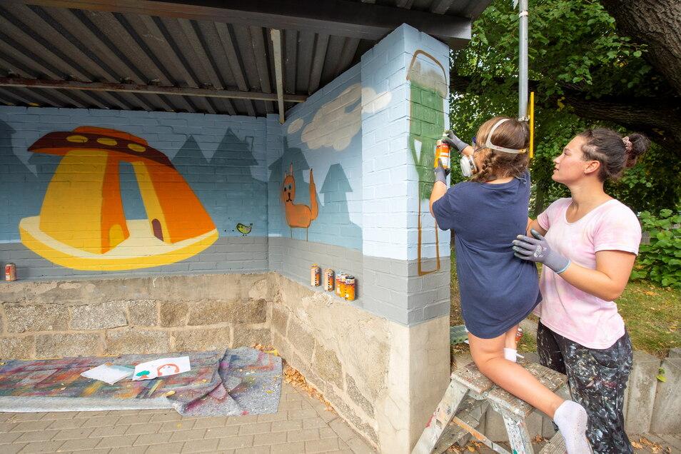 Praktikantin Luisa Gawalski hilft Anna-Lena beim Aufsprühen der Farbe an der Bushaltestelle Lampertswalde. Hier wird Dynamo übermalt.