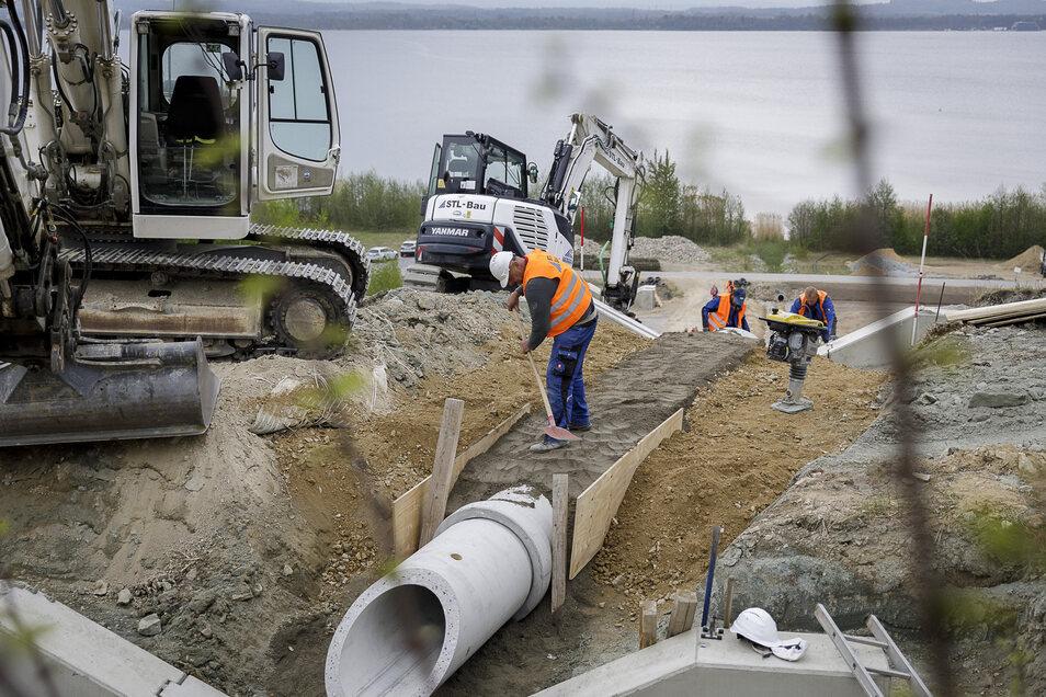 Arbeiter sind derzeit dabei, einen beschädigten Regenwasserabsturz am Westufer des Berzdorfer Sees zu erneuern. Den asphaltierten Rundweg befahren sie dafür mit schweren Baufahrzeugen.