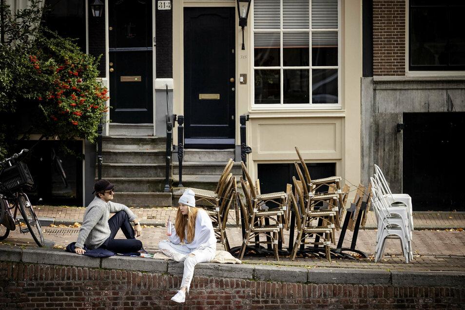 Menschen sitzen in Amsterdam vor einer Terrasse eines geschlossenem Catering-Unternehmens.