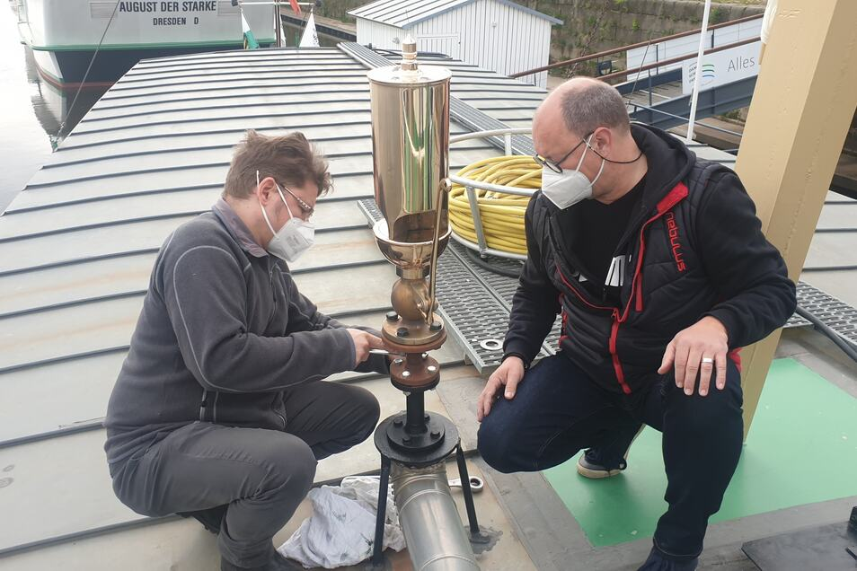 Falk Hering (l.) und Dirk Ebersbach bei der Montage der Wehlen-Pfeife auf dem Dampfer Pillnitz.