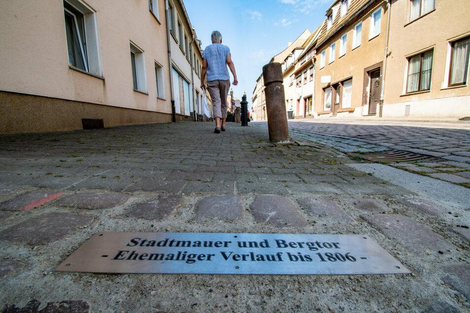 In der Nossener Straße in Roßwein haben Mitarbeiter des Bauhofes mit einer Platte im Gehwegpflaster den weiteren Verlauf der Stadtmauer veranschaulicht.