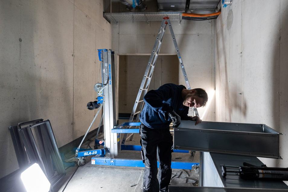 Gerade wurden alle Komponenten der riesigen Lüftungsanlage angeliefert. Lüftungsinstallateur Matrin Fenko passt die Rahmen an die Öffnungen im Beton an.