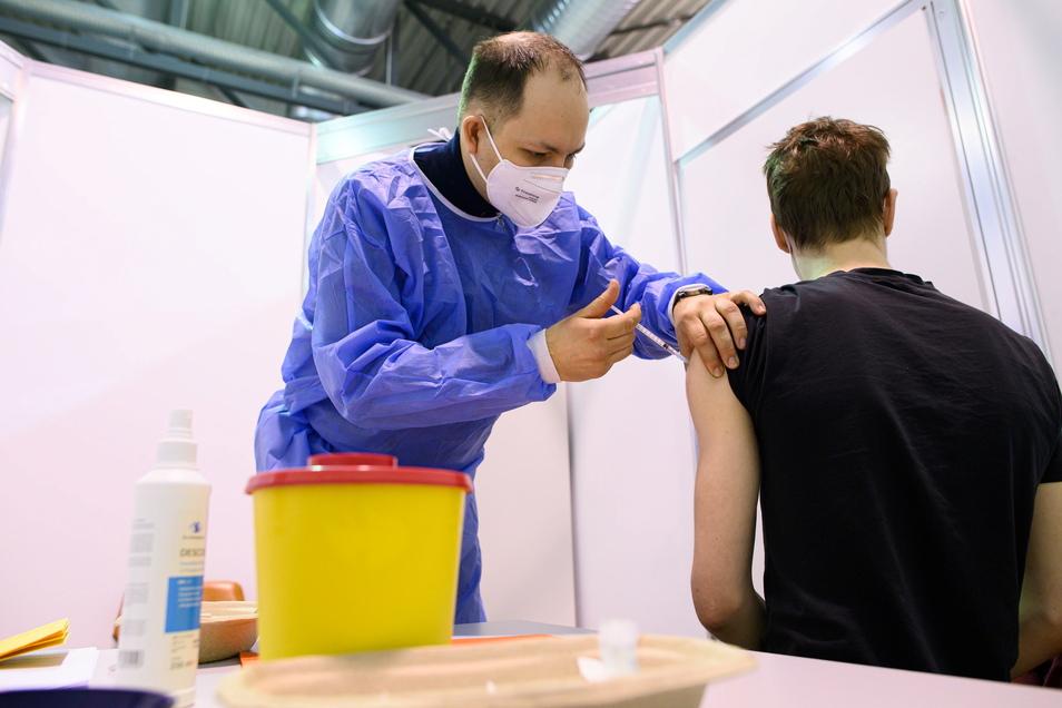 Impf-Neustart im Dresdner Impfzentrum: Ein Arzt verabreicht dort einem jungen Mann die Immunisierung mit dem Astrazeneca-Wirkstoff gegen Corona.
