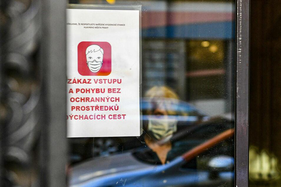An einem Fenster einer Postfiliale hängt ein Schild, welches die Menschen darauf hinweist, einen Mundschutz zu tragen. In Tschechien breitet sich das Coronavirus weiter rasant aus.