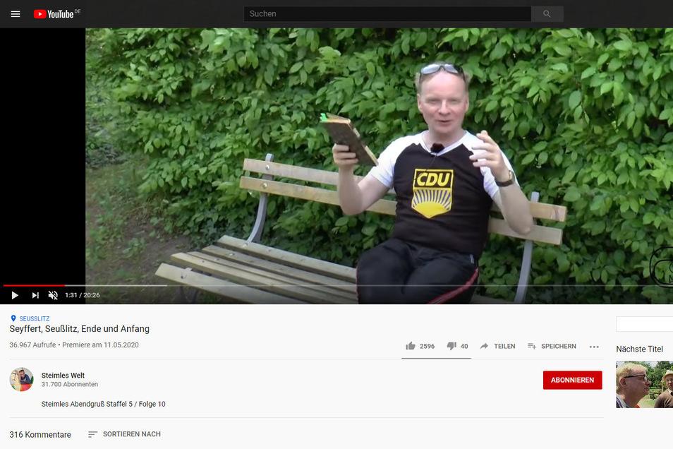 Uwe Steimle auf einer Bank im Seußlitzer Schlosspark. Deutlich zu erkennen ist das FDJ-Logo mit dem CDU-Schriftzug.