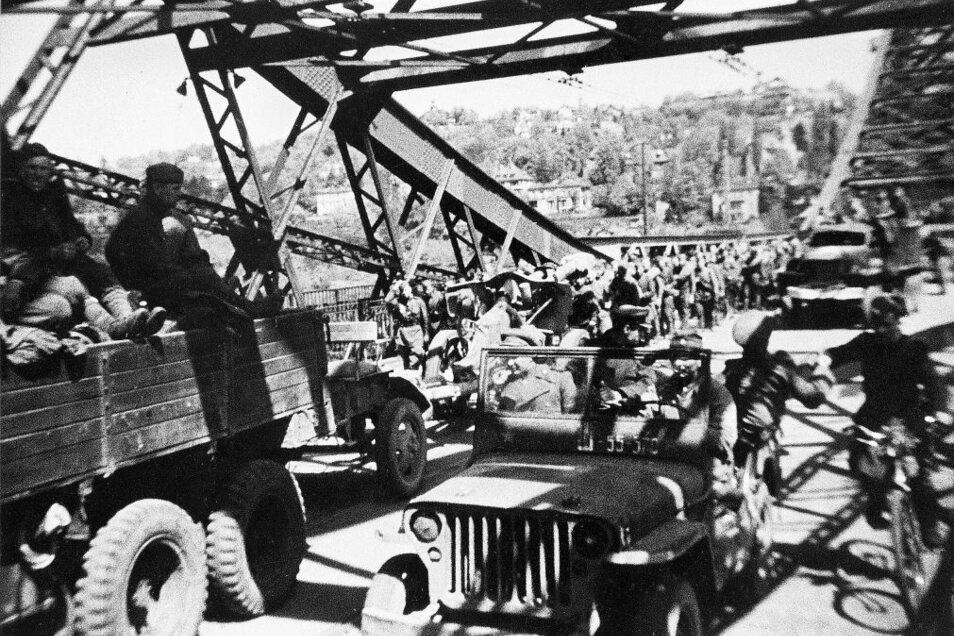 """Truppen der Roten Armee rollen über das """"Blaue Wunder"""" in Dresden ein; Szene aus einem sowjetischen Dokumentarfilm."""