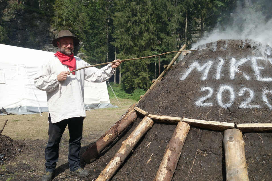 Jirí Kadera sticht Löcher in die oberste Deckschicht, damit die Holzkohle gleichmäßig abbrennt. Bis Sonntag ist der Meiler in Betrieb.
