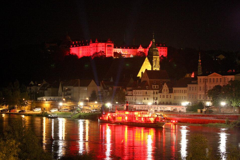 Blick auf Pirna am Montagabend: Für die Protestaktion Night of Light haben Veranstalter bundesweit Gebäude rot angestrahlt, um auf ihre Notlage in der Corona-Krise aufmerksam zu machen.