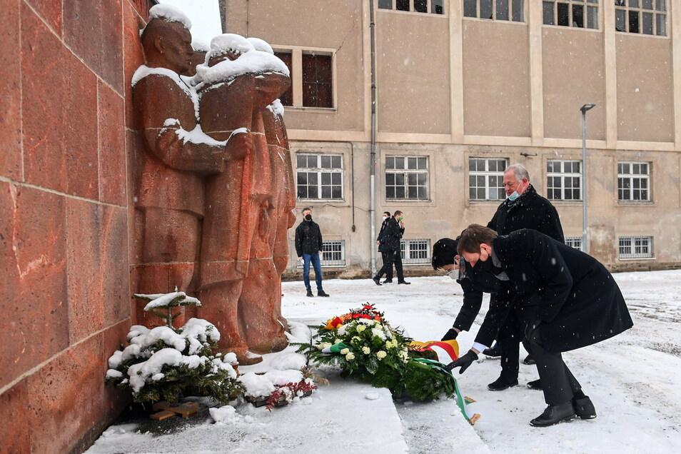Michael Kretschmer (CDU, v.r.), Ministerpräsident von Sachsen, Thomas Firmenich (CDU), Bürgermeister von Frankenberg, und Iris Firmenich, CDU-Landtagsabgeordnete, legen am Mahnmal der KZ-Gedenkstätte Sachsenburg Kränze nieder.