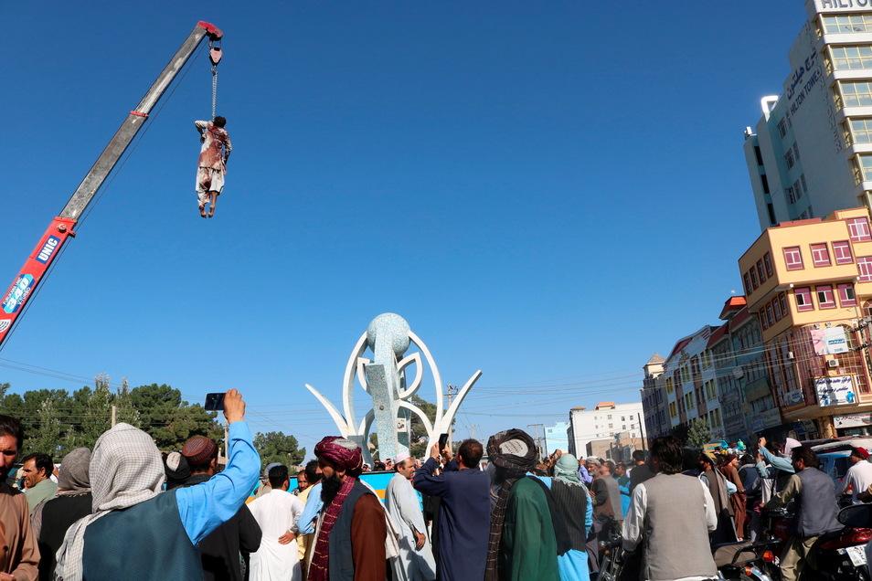 Eine Leiche hängt an einem Kran auf dem Hauptplatz der Stadt Herat im Westen Afghanistans und wird von Zuschauern gefilmt. Die Taliban haben die Leichen von vier Männern öffentlich aufgehängt, die einen Händler und seinen Sohn entführt haben sollen.