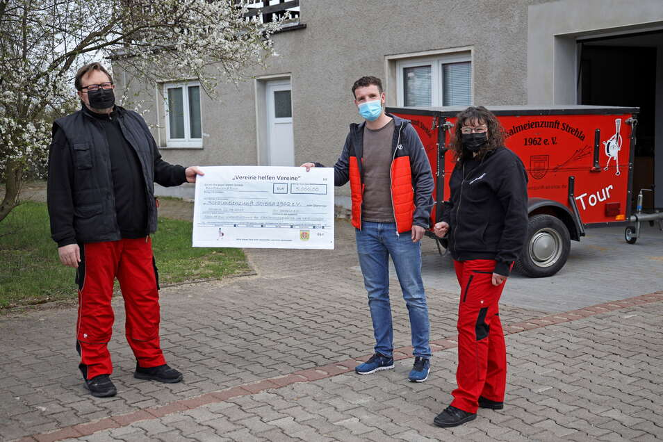 Die Vorstände der Strehlaer Schalmeienzunft Uwe Boczek (l.) und Ilka Staude (r.) erhielten vom Vorsitzenden des SV Strehla Felix Naumann (M.) jetzt eine Spende über 5.000 Euro. Damit unterstützen die Sportler die Musiker beim Umbau von deren neuem Vere