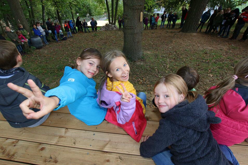 Evely, Maria und Helene sitzen mit ihren Mitschülern auf einem der drei Holzdecks, die im Mußepark an der evangelischen Grundschule entstanden sind.