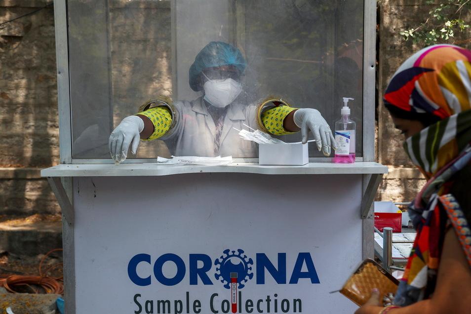 Eine Mitarbeiterin des Gesundheitswesens pausiert in einer Corona-Teststation, wo Nasenabstriche entnommen werden. Die Corona-Zahlen in Indien steigen seit Wochen schnell an, Krankenhäuser sind nach wie vor überfüllt und Sauerstoff rar.