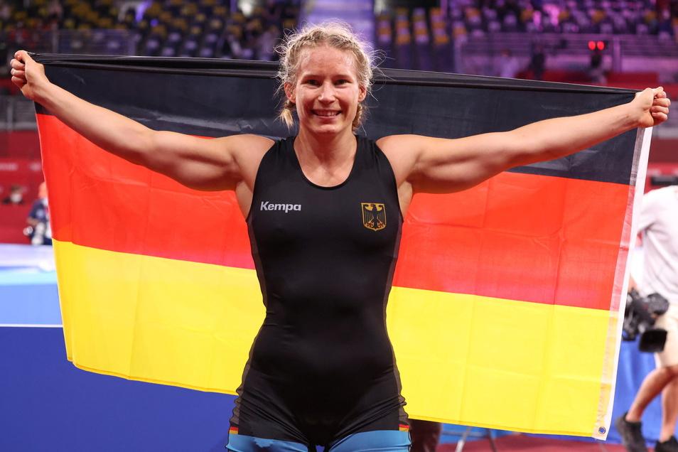 Eine Einheit: Aline Rotter-Focken feiert ihren Olympiasieg ausgiebig mit der deutschen Fahne.