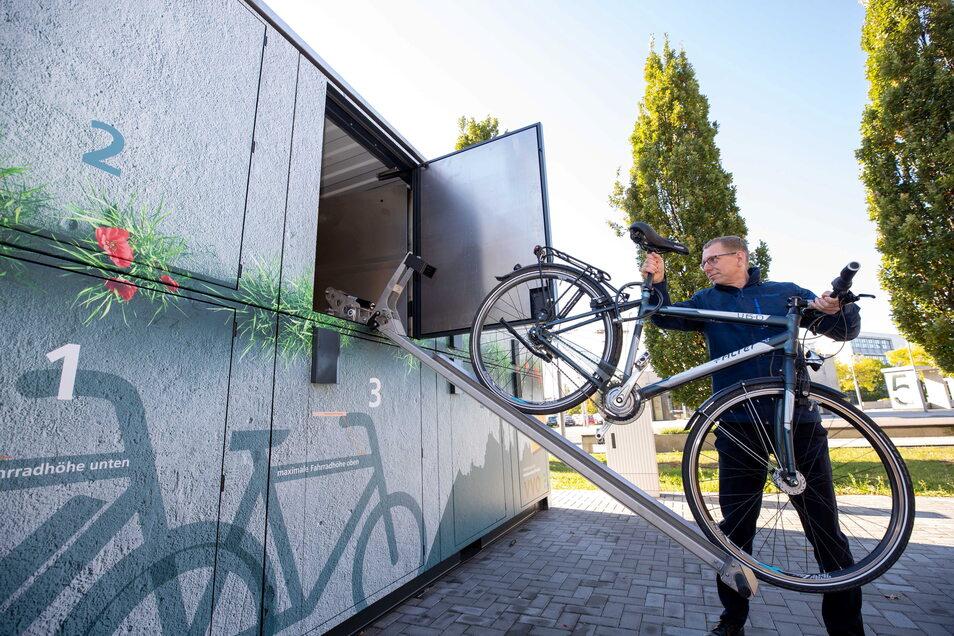 Selbsttest an der neuen Fahrradgarage: Pirnas Bürgermeister Markus Dreßler bugsiert sein Rad in eine der oberen Boxen - was mit technischer Hilfe mühelos gelingt.