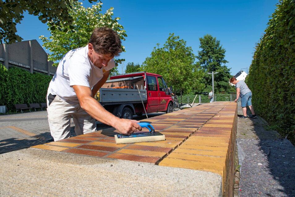 Uwe Krüger von der Baugesellschaft Großenhain ist seit ein paar Tagen mit der Neuverfugung von Klinkerbänken am Nixplatz beschäftigt.
