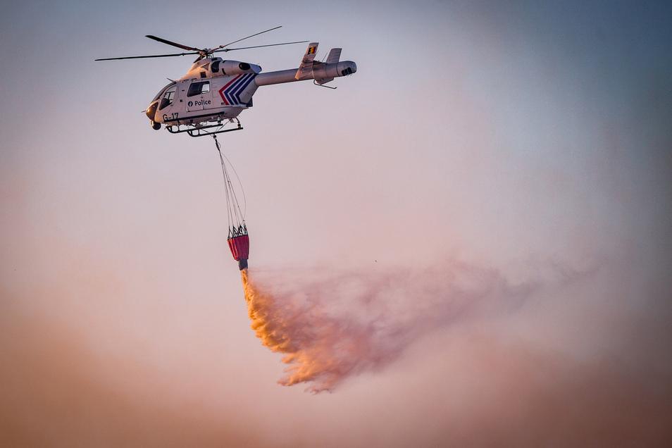 """Mit Hilfe eines Hubschraubers wird aus der Luft versucht das Feuer im belgischen Naturschutzgebiet """"De Liereman"""" zu löschen."""