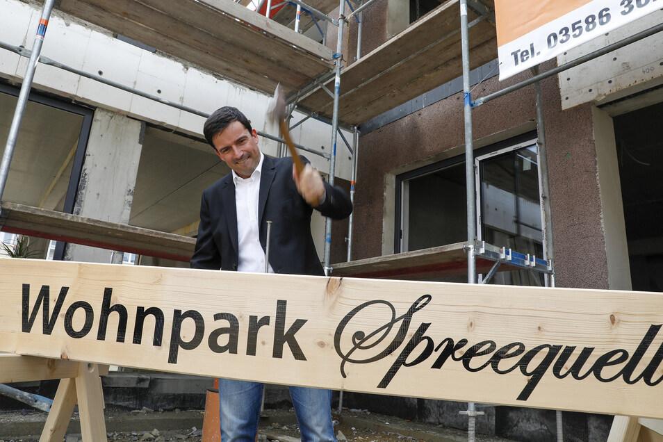 Baufortschritt mit Schwung: WBG-Vorstand Daniel Füssel schlug beim Richtfest den symbolischen letzten Nagel in den Balken.