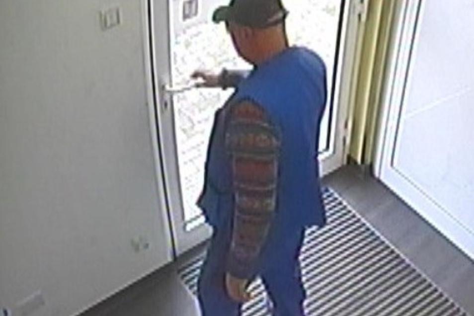 Der gesuchte mutmaßliche Betrüger warblauer Arbeitskleidung und einem dunklen Basecap bekleidet