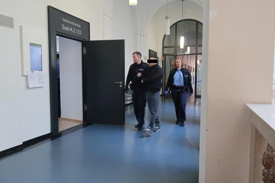Einer der vier Kuriere aus Lübeck wird von Wachtmeistern in den Gerichtssaal gebracht. Nach einem halben Jahr in Untersuchungshaft kamen die Angeklagten nun auf freien Fuß.
