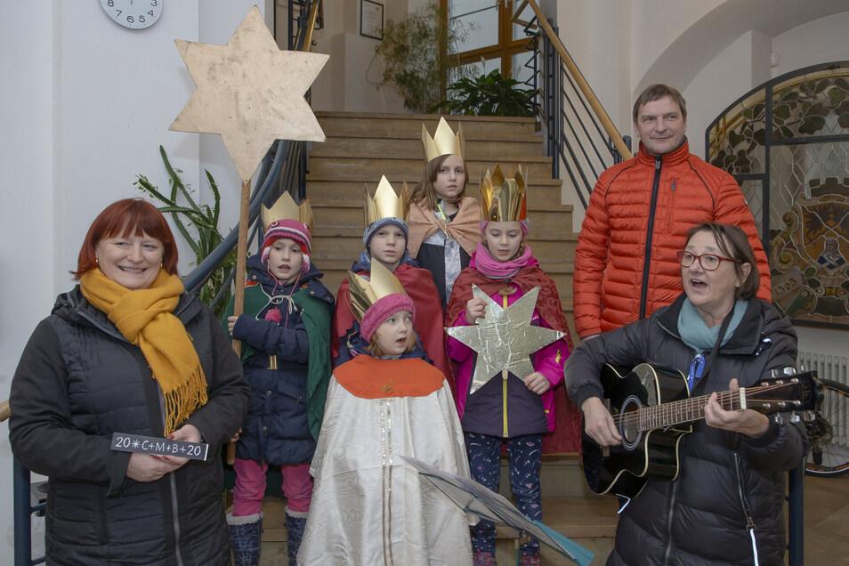 Chorleiterin Elke Klein-Nowoiskyspielt Gitarre und  singt mit den Sternsingern Magdalena, Amelie, Carlo, Saskia, Greta ein Segenslied für die Spitze der Stadtverwaltung Dipps.