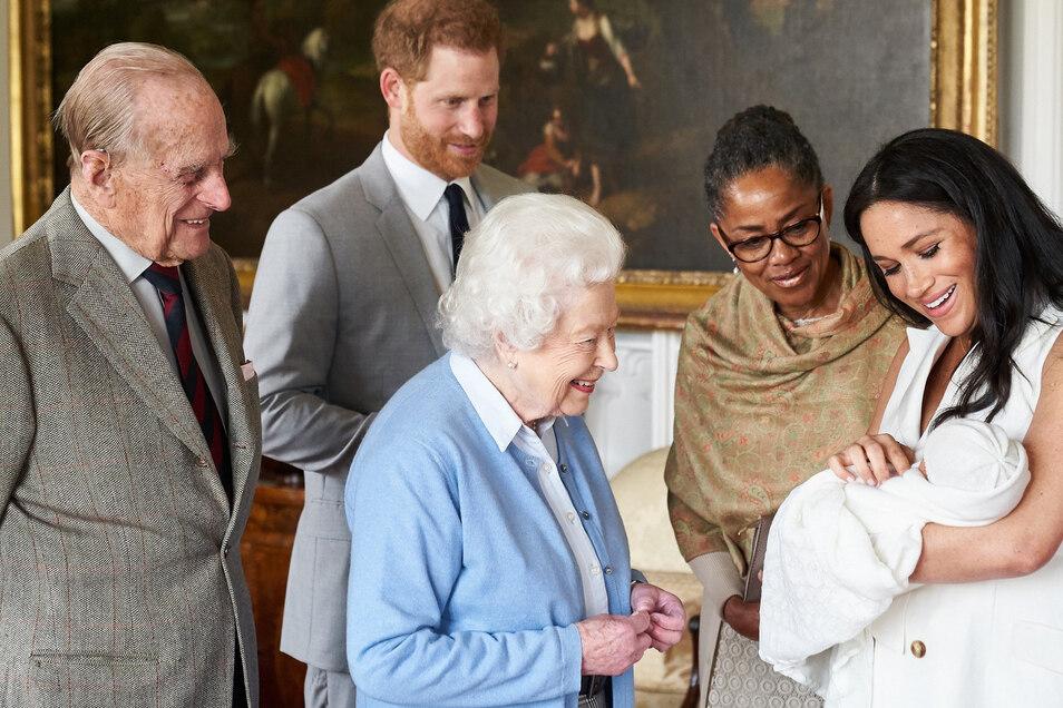 Herzogin Meghan (r) zeigt zusammen mit Prinz Harry (2.v.l) ihren Sohn Archie Harrison Mountbatten-Windsor dessen Uroma Königin Elizabeth II. (M), dem Herzog von Edinburgh (l) und ihrer Mutter, Doria Ragland (2.v.r).