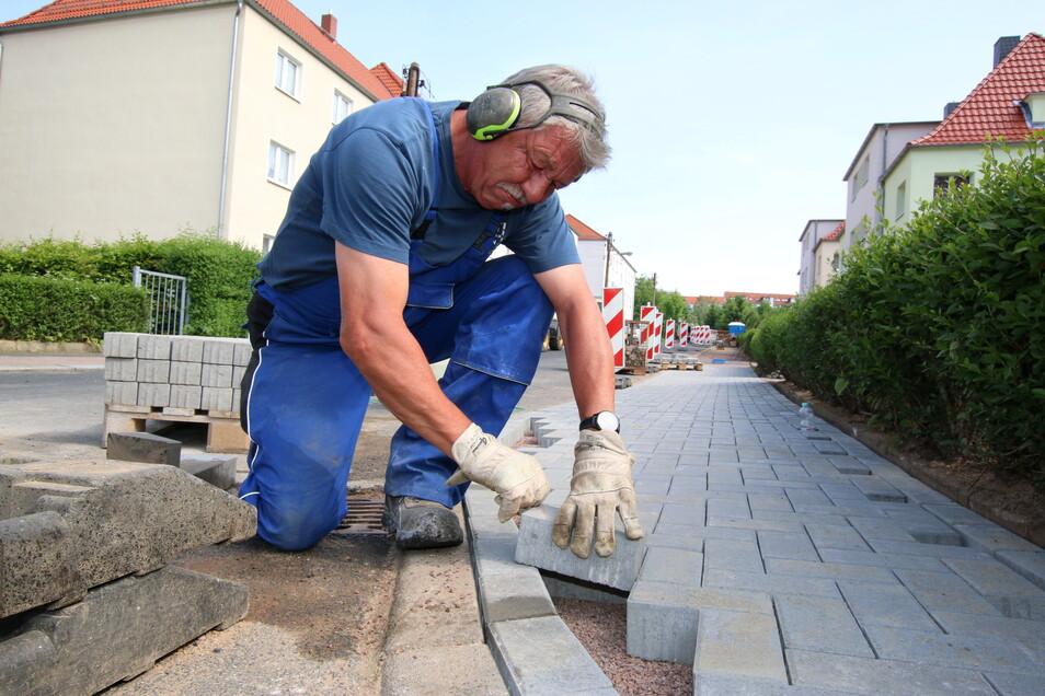 Steffen Ebert bereitet die Randsteine für den neu entstandenen Gehweg an der Ziegeleistraße in Roßwein vor.