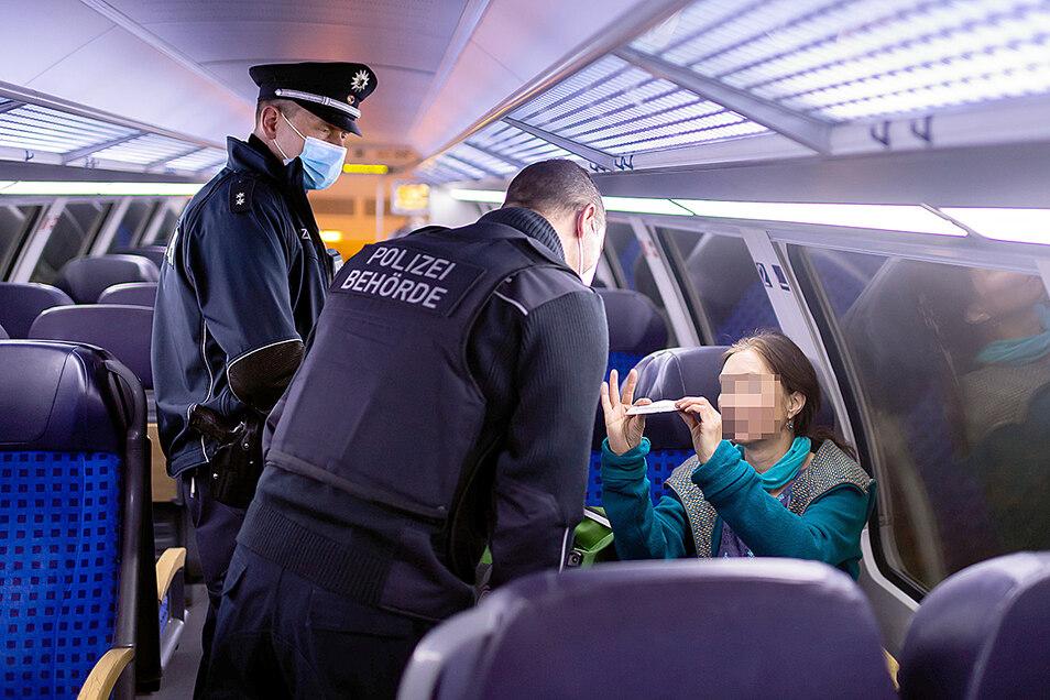 Das Attest befreit von der Maske: Eine Reisende zeigt dem Kontrollteam ihre ärztliche Bescheinigung. Auch Behindertenausweise gelten als Befreiung.