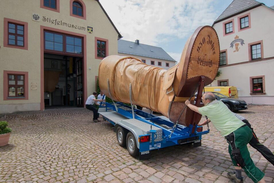 Mit vereinten Kräften wird der Leisniger Riesenstiefel nach seiner Sanierung zurück ins Museum geschoben.