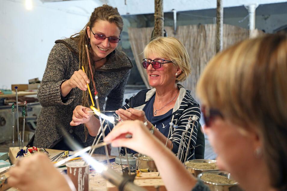 Kursleiterin Henriette Preuß (l.) zeigt Teilnehmerin Barbara Heinrich verschiedene Kniffe, um heißes Glas per Brenner in Form zu bringen. Den Glaskunstkurs gab es dieses Jahr bei der Sommerakademie zum ersten Mal.