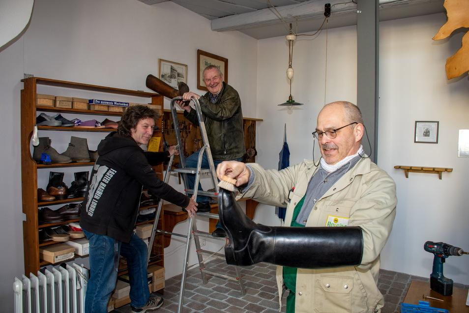 Frank Geißler, Rolf Neidhardt und Uwe Reichel (von links) haben sichtlich Spaß beim Wiedereinrichten des Stiefelmuseums auf dem Leisniger Burglehn. Die Kur des großen Stiefels hat die Kommune genutzt, um den Raum vorzurichten.