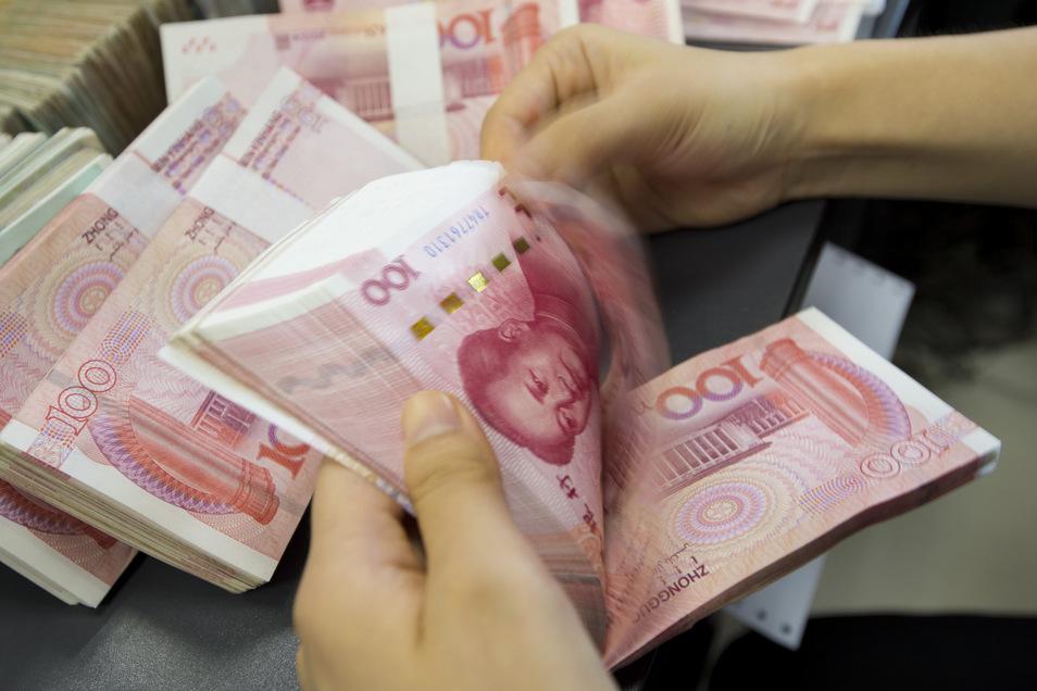 Eine Bankangestellte zählt ein Bündel Yuan-Geldscheine (Symbolfoto).
