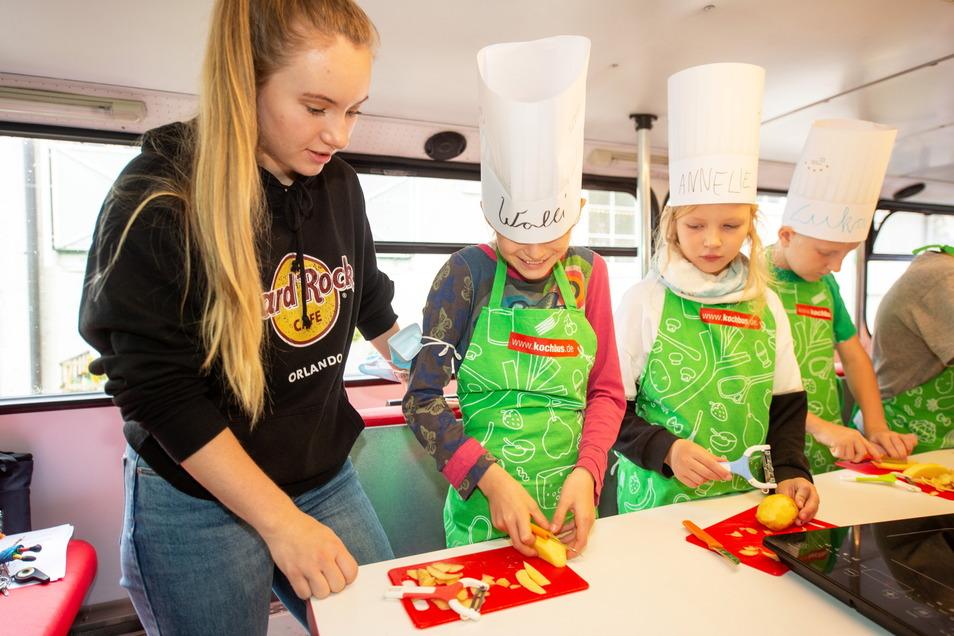 Lukas, Annelie und Walli bekommen von Praktikantin Mara Opitz (v.r.n.l.) Hilfe, Kartoffeln für Pommes in Scheiben zu schneiden. Dabei hat Walli nicht nur mit klitschigen Erdäpfeln zu kämpfen, sondern auch mit der rutschenden Kochmütze.