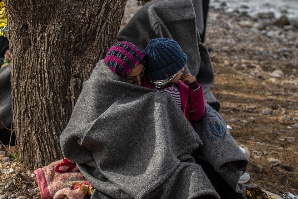 Migranten aus Afghanistan sitzen nach ihrer Ankunft auf der griechischen Insel Lesbos am Strand.