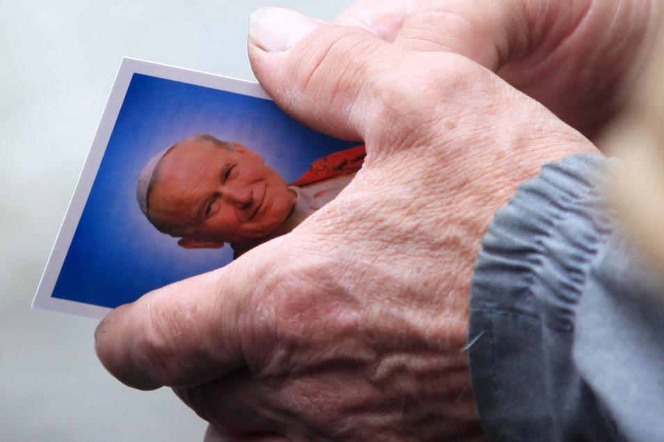 Polen, Wadowice: Ein Postkartenporträt des verstorbenen Papstes Johannes Paul II. in den Händen eines Ortsansässigen vor der Marienbasilika, als sich Zehntausende versammelten, um die Seligsprechung des in Wodowice geborenen Karol Wojtyla zu feiern.