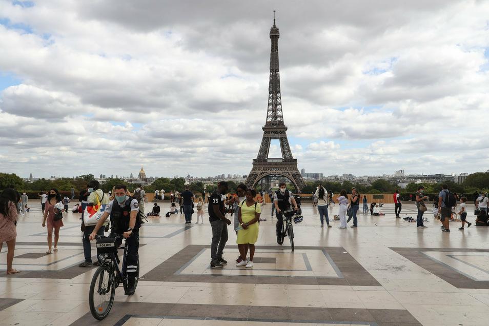 Fahrradpolizisten mit Gesichtsmasken patrouillieren auf der Esplanade Trocadero in der Nähe des Eiffelturms.