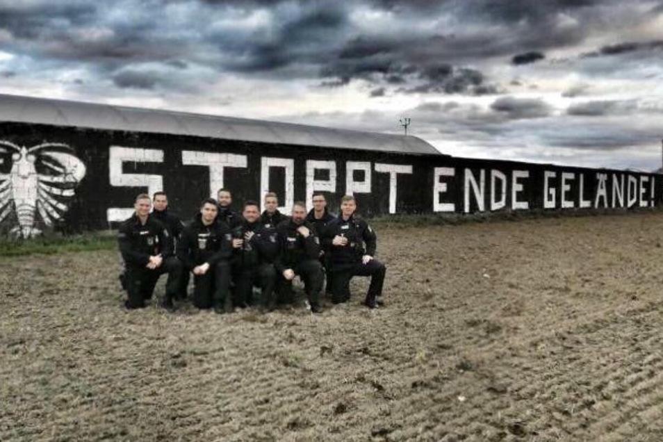 """Umstrittenes Foto: Polizisten posieren vor dem Spruch """"Stoppt Ende Gelände""""."""