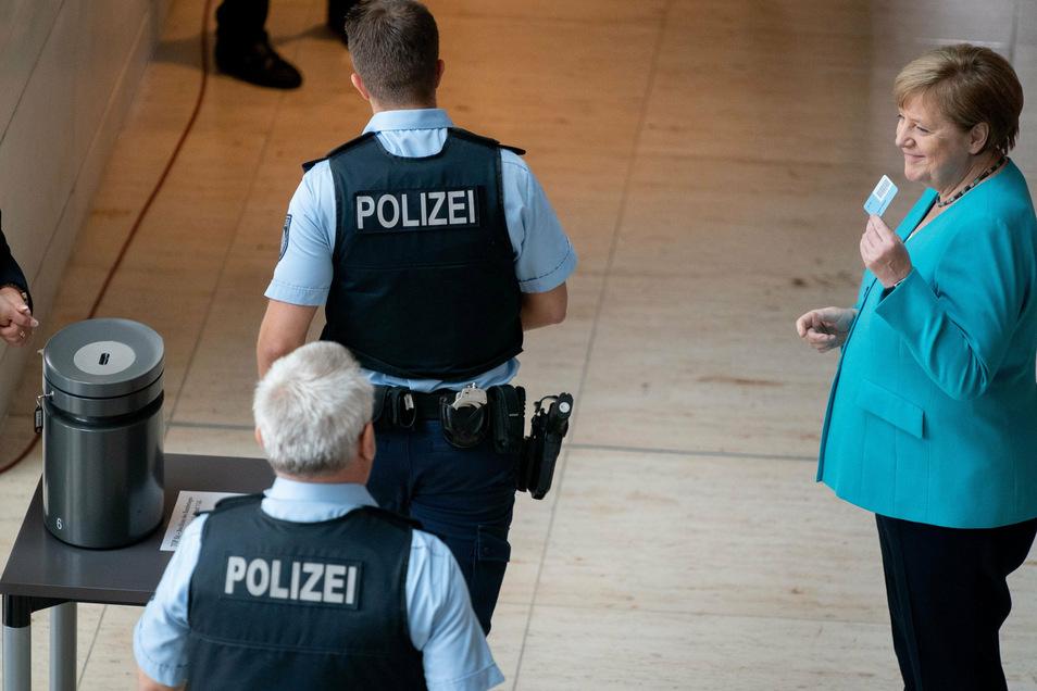 Bundeskanzlerin Angela Merkel steht neben Polizeibeamten im Bundestag.