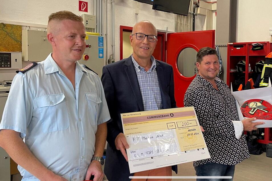 Torte statt vieler Worte und eine Spende: Diese Geschenke überbrachten die Stadträte Uwe Reichel (rechts) und Oliver Morof an Meißens Stadtwehrleiter Frank Fischer zu einem großen Jubiläum.