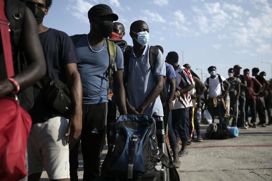 Geflüchtete Menschen stehen vor einem provisorischen Camp auf Lesbos Schlange.
