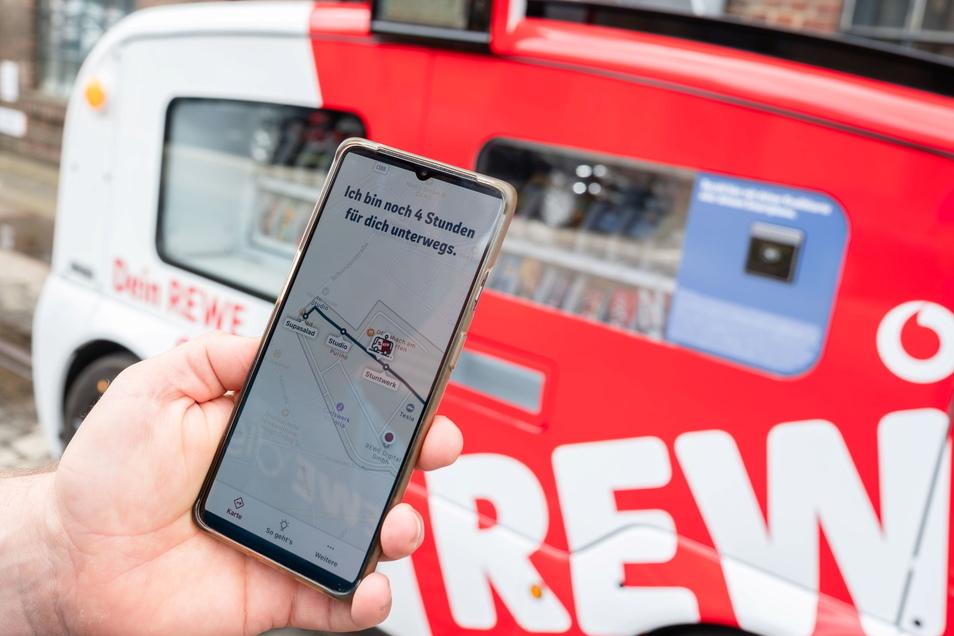 """Frank Schmitz, Projektleiter von REWE digital, zeigt auf seinem Mobiltelefon eine App, auf dem sich die Route des """"Snack Mobils"""" verfolgen lässt."""