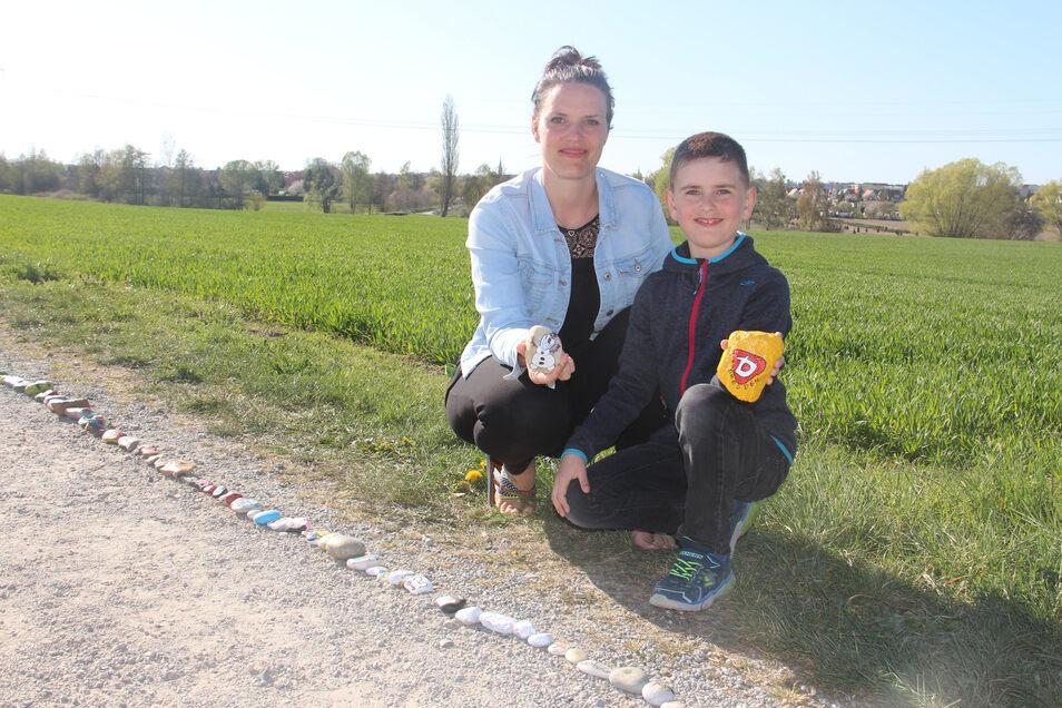 Sandra Mittasch und ihr Sohn Louis freuen sich, dass, die Schlange aus bemalten Steinen in Auritz immer weiter wächst.