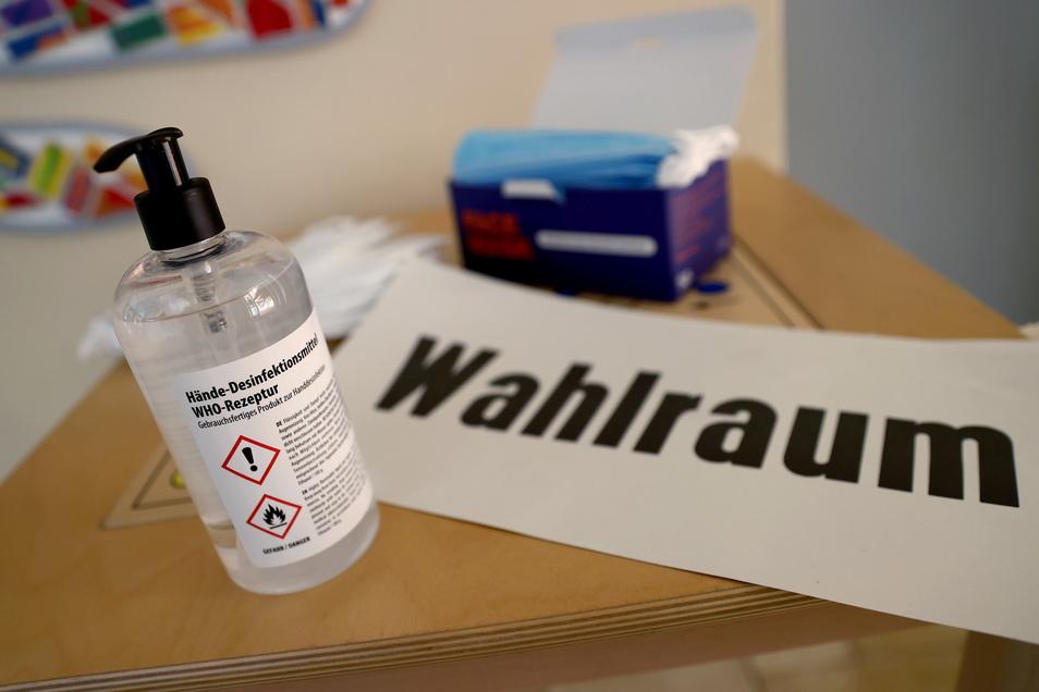 Eine Flasche mit Desinfektionsmittel steht in einem Wahllokal neben dem Schild Wahlraum. Offensichtlich hat es geholfen. Die Inzidenz im Landkreis Meißen ist am Montag auf 36,2. gefallen.