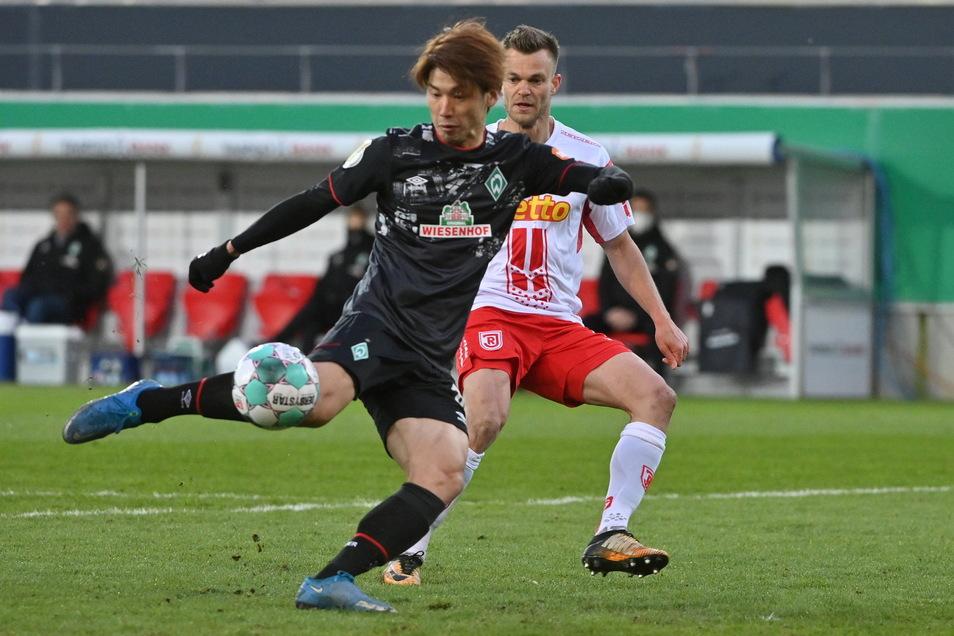 Bremens Yuya Osako und Regensburgs Benedikt Saller (r) in Aktion.