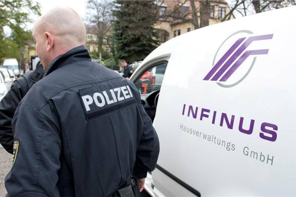 Ein Polizeibeamter steht während der Razzia in einem Objekt der Infinus AG am Vogesenweg in Dresden neben einem Fahrzeug der Firma.