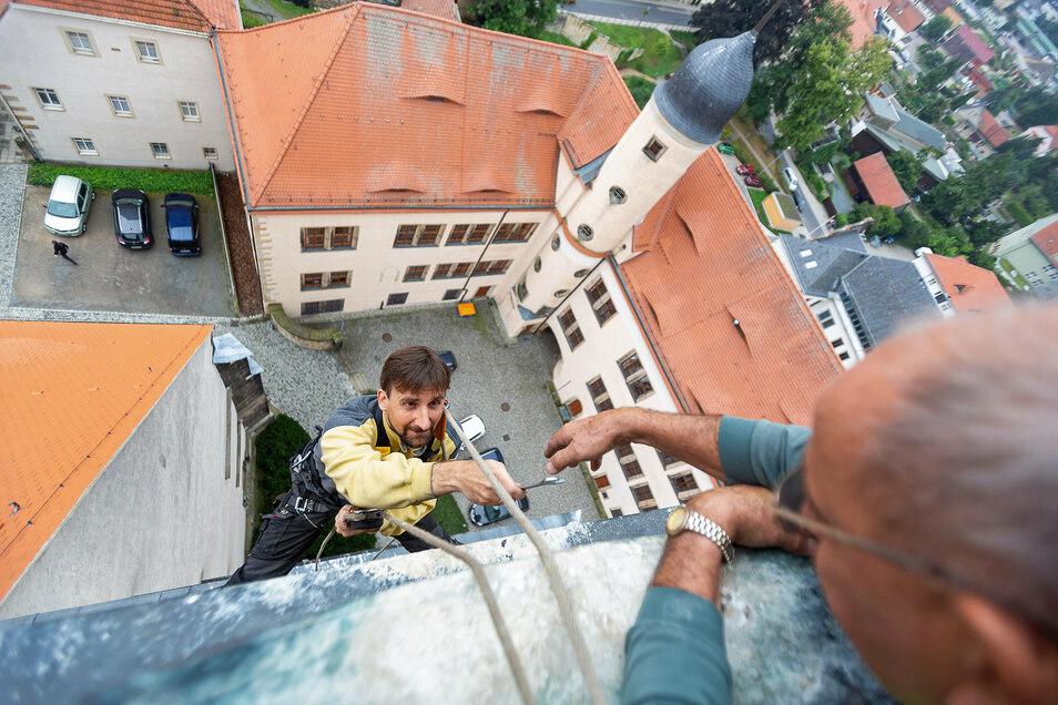Tobias Vogler hängt am Kirchturm über den Dächern von Dippoldiswalde. Kirchner Andreas Kunath reicht ihm Werkzeug, das für einen Uhrmacher riesig ist.