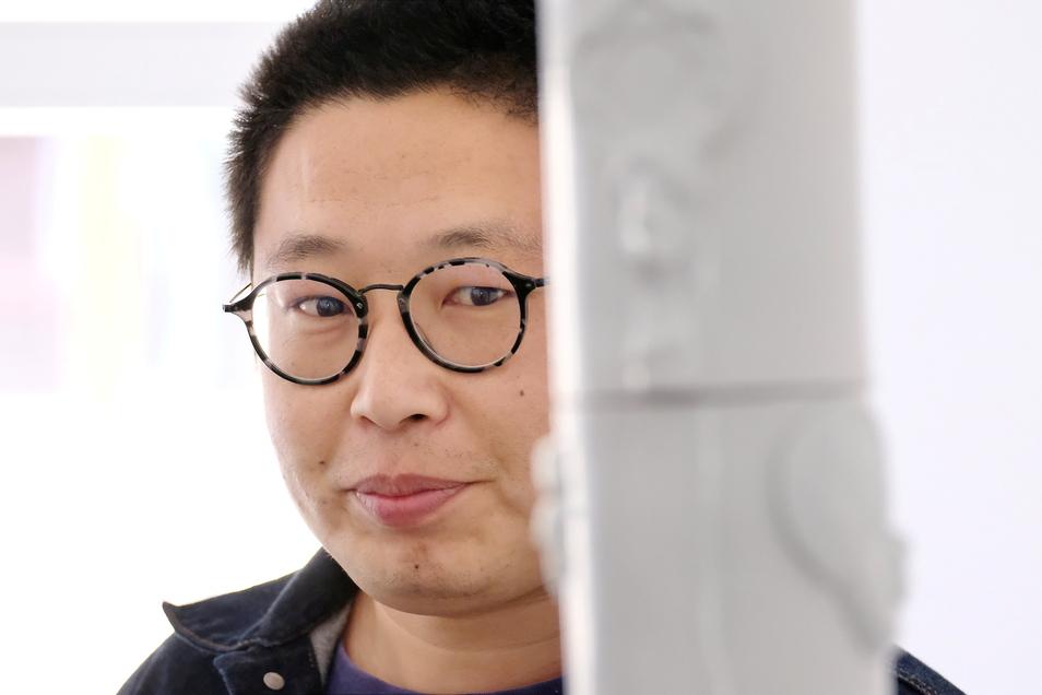 Prüfender Blick aufs eigene Werk: Der chinesische Künstler Zhuo Qi hat sich mit einer Ausstellung hier geschaffener Werke nach acht Wochen aus Meißen verabschiedet.