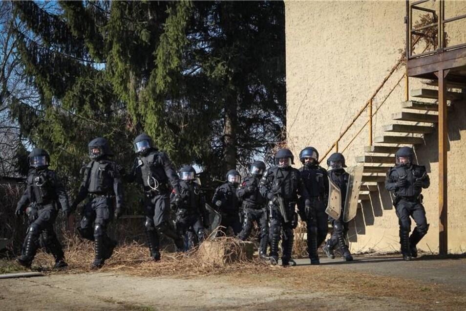 Martialisch uniformiert verschafft sich die Polizei Zutritt zum Gelände.
